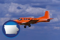 iowa a red turboprop aircraft flying in a blue sky with cumulus clouds