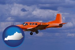 kentucky a red turboprop aircraft flying in a blue sky with cumulus clouds