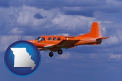 missouri a red turboprop aircraft flying in a blue sky with cumulus clouds