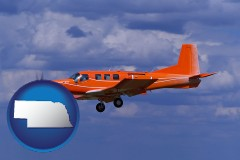 nebraska a red turboprop aircraft flying in a blue sky with cumulus clouds