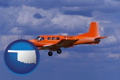 oklahoma a red turboprop aircraft flying in a blue sky with cumulus clouds
