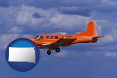 south-dakota a red turboprop aircraft flying in a blue sky with cumulus clouds