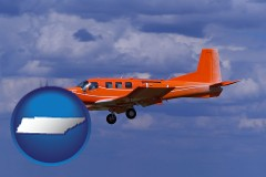 tennessee a red turboprop aircraft flying in a blue sky with cumulus clouds