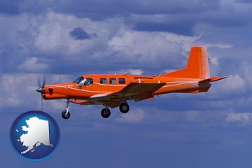 a red turboprop aircraft flying in a blue sky with cumulus clouds - with Alaska icon