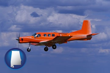 a red turboprop aircraft flying in a blue sky with cumulus clouds - with Alabama icon