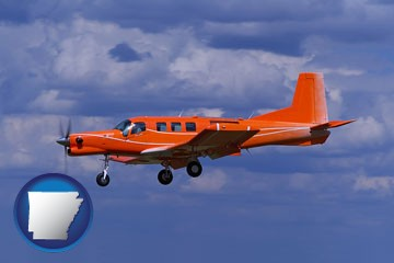 a red turboprop aircraft flying in a blue sky with cumulus clouds - with Arkansas icon