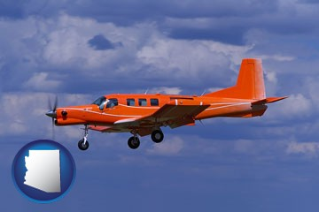 a red turboprop aircraft flying in a blue sky with cumulus clouds - with Arizona icon