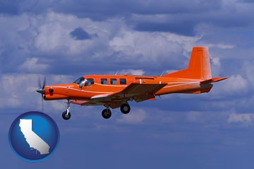 a red turboprop aircraft flying in a blue sky with cumulus clouds - with California icon