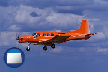 a red turboprop aircraft flying in a blue sky with cumulus clouds - with Colorado icon