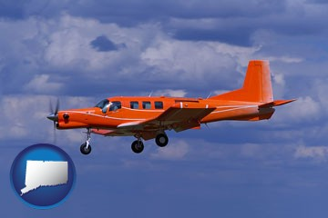 a red turboprop aircraft flying in a blue sky with cumulus clouds - with Connecticut icon