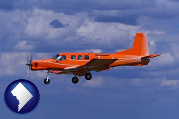 a red turboprop aircraft flying in a blue sky with cumulus clouds - with Washington, DC icon