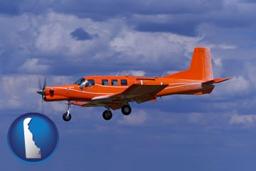a red turboprop aircraft flying in a blue sky with cumulus clouds - with Delaware icon