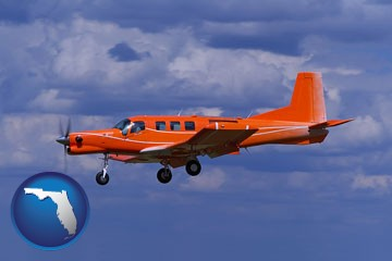 a red turboprop aircraft flying in a blue sky with cumulus clouds - with Florida icon