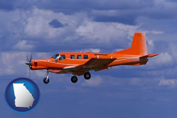 a red turboprop aircraft flying in a blue sky with cumulus clouds - with Georgia icon