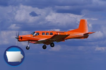 a red turboprop aircraft flying in a blue sky with cumulus clouds - with Iowa icon