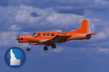 a red turboprop aircraft flying in a blue sky with cumulus clouds - with Idaho icon
