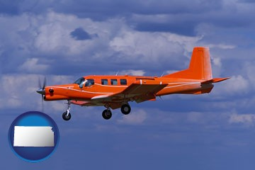 a red turboprop aircraft flying in a blue sky with cumulus clouds - with Kansas icon