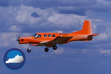a red turboprop aircraft flying in a blue sky with cumulus clouds - with Kentucky icon