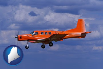 a red turboprop aircraft flying in a blue sky with cumulus clouds - with Maine icon