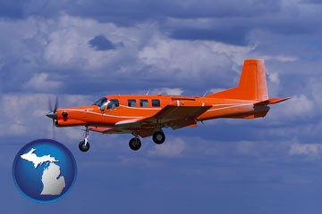 a red turboprop aircraft flying in a blue sky with cumulus clouds - with Michigan icon