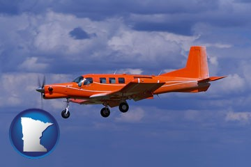 a red turboprop aircraft flying in a blue sky with cumulus clouds - with Minnesota icon