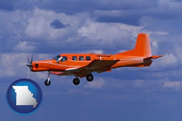 a red turboprop aircraft flying in a blue sky with cumulus clouds - with Missouri icon