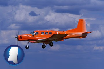 a red turboprop aircraft flying in a blue sky with cumulus clouds - with Mississippi icon