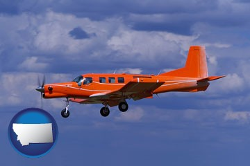 a red turboprop aircraft flying in a blue sky with cumulus clouds - with Montana icon