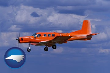 a red turboprop aircraft flying in a blue sky with cumulus clouds - with North Carolina icon