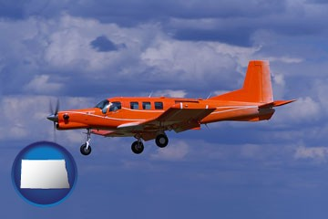 a red turboprop aircraft flying in a blue sky with cumulus clouds - with North Dakota icon