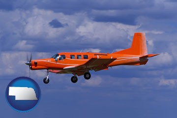 a red turboprop aircraft flying in a blue sky with cumulus clouds - with Nebraska icon