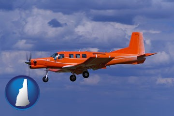 a red turboprop aircraft flying in a blue sky with cumulus clouds - with New Hampshire icon