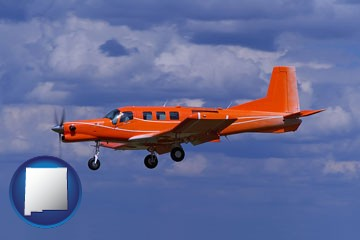 a red turboprop aircraft flying in a blue sky with cumulus clouds - with New Mexico icon