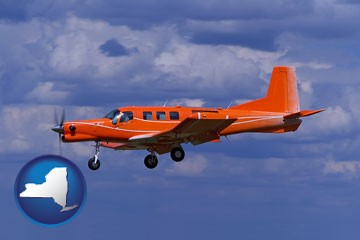 a red turboprop aircraft flying in a blue sky with cumulus clouds - with New York icon