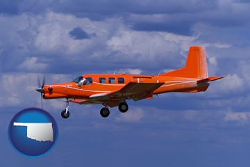 a red turboprop aircraft flying in a blue sky with cumulus clouds - with Oklahoma icon