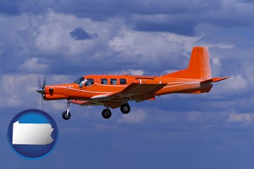 a red turboprop aircraft flying in a blue sky with cumulus clouds - with Pennsylvania icon