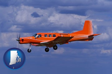 a red turboprop aircraft flying in a blue sky with cumulus clouds - with Rhode Island icon