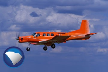 a red turboprop aircraft flying in a blue sky with cumulus clouds - with South Carolina icon