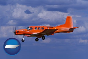 a red turboprop aircraft flying in a blue sky with cumulus clouds - with Tennessee icon