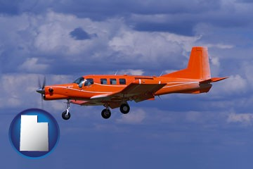 a red turboprop aircraft flying in a blue sky with cumulus clouds - with Utah icon