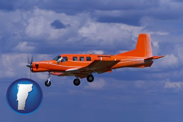 a red turboprop aircraft flying in a blue sky with cumulus clouds - with Vermont icon