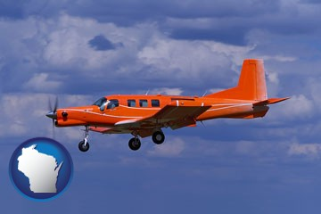 a red turboprop aircraft flying in a blue sky with cumulus clouds - with Wisconsin icon