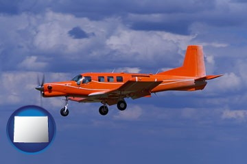 a red turboprop aircraft flying in a blue sky with cumulus clouds - with Wyoming icon