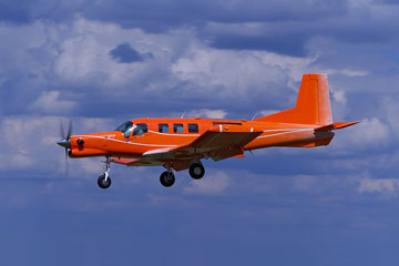 a red turboprop aircraft flying in a blue sky with cumulus clouds